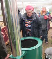 Villager Laura King observes a demonstration on how to build and top-light the InStove's fire.