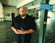 Braddock Mayor John Fetterman stands in the living area of his Braddock home, a building which was once a car dealership.