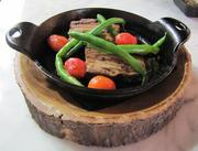 A braised lamb belly is cooked in a cast-iron skillet and accompanied by plum tomatoes and crispy green beans. It is served in the skillet on a handmade platter made, as you can see, out of what was recently a tree.