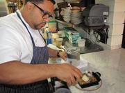 Chef Kevin Sbraga adds homemade vanilla ice cream to a chocolate chip cookie dessert served hot from the oven in a cast-iron pan.