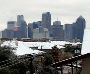 The Dallas skyline rises above ice-covered rooftops in Uptown.