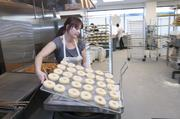 Laura Wolken, manager at Voodoo Doughnut, makes the first batch in the Denver store. Wolken moved from Portland.