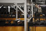 An employee descends a ladder after checking on automated systems that sort packages.