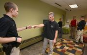 Instructor Mike Ardolf (center) teaches law enforcement skills student Jason Elasky (left) proper technique for taking information from a suspect by standing in as a domestic dispute suspect.