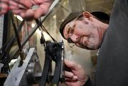 Mike Buckley, in the crossbow riser assembly area stringing a Recruit compound bow.
