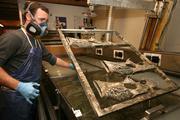 Eric Hinton, dipper in the water transfer printing department, printing camouflage gun stocks.