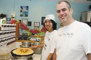 Chris Tarvyd, right, co-owner of Crepes No Ka Oi, and worker Devinn Zakahi prepare customer orders at the Kailua crepe business.