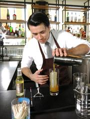 Johnny Schaefer pouring a signature drink at Moxie Kitchen + Cocktails, where he is bar manager.