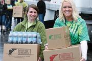 Univera Healthcare employees Jessica Haahr, left, and Michele Hrichan distribute food at the annual community event hosted by the Belle Center of Buffalo. Each year Univera Healthcare provides most employees with eight hours of paid time to volunteer in the community.