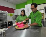 Carolina Montoya and Fernando Puga roll fondant onto a cake.