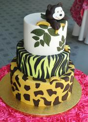 A tiered, animal-themed cake with fondant decorations.