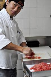 A cook preparing the tuna.