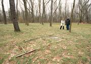 Penn Forest Natural Burial Park manager Pete McQuilin and visitor Wendy Long near the gravesite of the first person buried in the 32-acre green cemetery. Since August 2011, four people have been buried there and 72 lots have been sold.