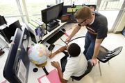 Sixth grade teacher Nicholas Keith follows closely as students work with their partners through the STEM modules.