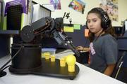 Sixth grader Vanessa Romero uses a computer to guide a robot through precise movements.