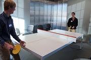 Calvin Dahms (left) and Evan Norris play pingpong on a surface that doubles as a conference table.