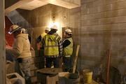 Construction workers discuss and work on DPAC's interior.