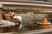Cook Juan Estrada moves on to the next order after putting up a lunch order at Tavern in the Square in Burlington, Mass.