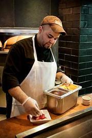 Not Your Average Joe's pizza maker Angel Rico prepares a desert in the Arlington, Mass. restaurant.