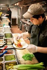 Not Your Average Joe's cook Pablo Rosas preps a luncheon order in the Arlington, Mass. restaurant.