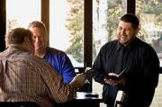 Tavern in the Square waiter Derek Jones offers friendly service to customers of the Burlington, Mass., restaurant.