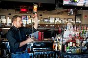 """Bartender Josh Dickey pours a """"tall"""" one at Tavern in the Square in Burlington, Mass., restaurant."""