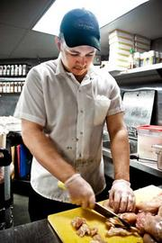Julio Chaves prepares chicken at Tavern in the Square in Burlington, Mass., restaurant.