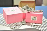 Warm cookies are delivered from Cookie Cab's ovens to your doorstep in these pink boxes and checkered tissue paper.