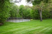 The property has a hard-surface tennis court and a carriage house.