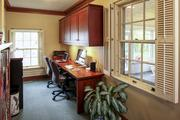 The library includes an area for an office with built-in desk and bookcases.