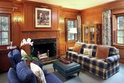The library has pine-paneled walls and a wood-burning fireplace, plus a three-quarter bathroom with marble shower.