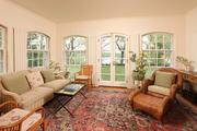 A sunroom features antique wide-planked oak floors, arched deep double-hung windows, a built-in sound system and views of Long Lake.