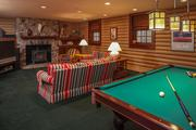 The amusement room has a gas stove, built-in sound system, split-log-paneled walls and room for a billiards table.