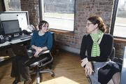 Chris Hoffmann, left, and Andi Ferguson share a back-to-back workspace, and can easily confer about company business.