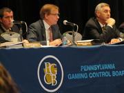 William H. Ryan Jr., chairman of the Pennsylvania Gaming Control Board (center), and board member Gregory C. Fajt at Tuesday's casino suitability hearings at the Pennsylvania Convention Center.
