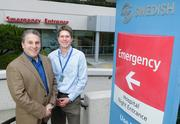 Howard Mahran, CEO and founder of Deep Domain, left, and Dr. Chris Dale, medical director of quality and value at Swedish Medical Group, stand by the  by the Emergency Department entrance at Swedish's First Hill campus, where a  data-driven case study by Deep Domain enabled Swedish  to dramatically reduce the time from door to doctor.