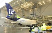 """Crews and media people look at a Boeing 747-8 freighter painted in a Seattle Seahawks colors and slogans, including """"12"""" for """"12th Man,"""" at the Boeing Everett plant."""