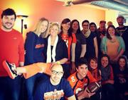 """Cohn Inc., Denver, www.cohnmarketing.com -- """"We're definitely United In Orange here at Cohn! For the last two Fridays we've had United In Orange and 2Nited in Orange (we thought we were pretty clever with that one!) events which included a completely orange and blue breakfast spread (think blueberries, cantaloupe, oranges, blueberry and carrot muffins, etc!), a squares score pool and everyone decked out in orange. We all crammed in front of our orange wall to commemorate the morning. All events, including the upcoming Super Bowl party, have been planned by a volunteer group of employees we call the Cohn Culture Club."""" -- Jackie"""