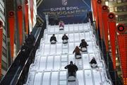 Fans sail down the toboggan ride on Super Bowl Boulevard.