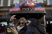 Fans stand for a photograph in front of a Macy's Inc. store before visiting Super Bowl Boulevard.