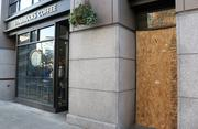 At right, a window is boarded up Monday at a Starbucks store on the corner of 1st Avenue and Yesler Way in Seattle's Pioneer Square area, where thousands of people celebrated in the streets Sunday night after the Seattle Seahawks' Super Bowl win. For the most part, crowds were well behaved.