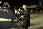 Seattle Seahawks Head Coach Pete Carroll shakes hands with Port of Seattle firefighters moments after the chartered Delta flight landed in Seattle with the Super Bowl Champions.