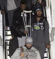 Seattle Seahawks Richard Sherman (center right with crutches) comes down the stairs of a chartered Delta flight with the Super Bowl Champions.