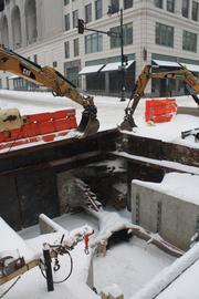 The snowstorm delays work at 13th and Main streets in Downtown.