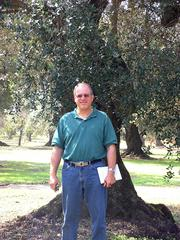DLM associate Ed Flohre poses with a 500-year-old olive tree at a farm in southern Italy from which DLM imports fine olive oils.