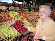 Vera Mayne, the major stockholder for most of DLM's history, stands in the produce section of a local store.