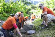 From left, Kaiser Permanente physician David Bell, with his son, Andrew, and Chris Lutz, director of clinic improvement process at Kaiser, building steps out of large stones at the Papahana Kualoa in Kaneohe.