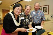 Lynette Lo Tom, owner of Bright Light Marketing, serves a prepared and donated lunch to the YMCA of Honolulu for the Y-Metro staff during a YMCA kickoff meeting for their annual support campaign. From left, Lynette Lo Tom, Michael Doss, executive vice president and chief operating officer for the YMCA of Honolulu and Michael Chinaka, senior vice president and chief financial officer.