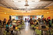 """The circular employee breakroom at Accent Marketing Services creates a community feel, said Kelly Hilton, vice president of corporate communications. The room is filled with bright colors and deinitions of the word """"community"""", along with illustrations of people doing activities outside."""