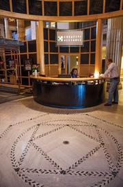 A cylinder-shaped wall encompasses the lobby area at Creative Alliance. The symbol on the floor, a feaure from the original building, coincendentally resembles Creative Alliance's logo.